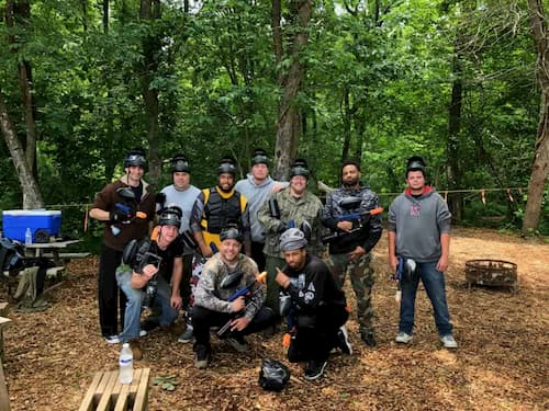 group of male paintball players on woods field