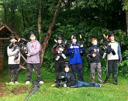 kids in woods playing paintball