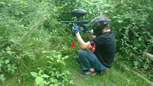 Boy shooting paintball gun on Pittsburgh woods field